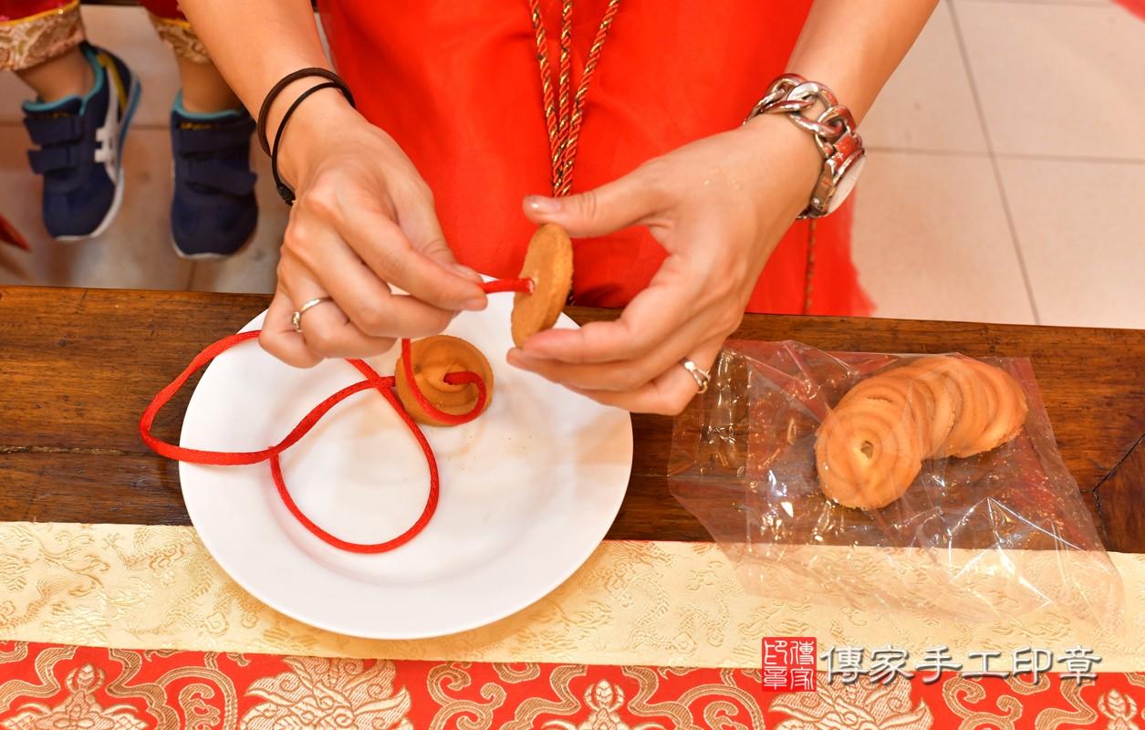 高雄市鳳山區陳寶寶古禮收涎祝福活動:為寶寶戴上收涎餅乾。照片2