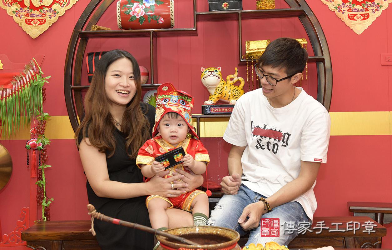爸爸媽媽幫寶寶戴上虎帽,虎爺可以保佑他平安健康長大喔。