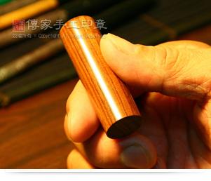 選擇適合的印章。範例的紫檀木印章呈現天然的年輪,為高級的印材之ㄧ。印材可選赤牛角或是紫檀木