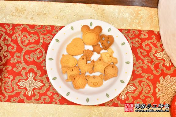 高雄市鳳山區翁寶寶古禮收涎祝福活動:為寶寶戴上收涎餅乾。照片1